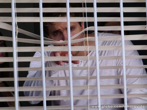 Ele fica com o coração apertado ao ver o menino pela janela (Foto: Amor à Vida / TV Globo)
