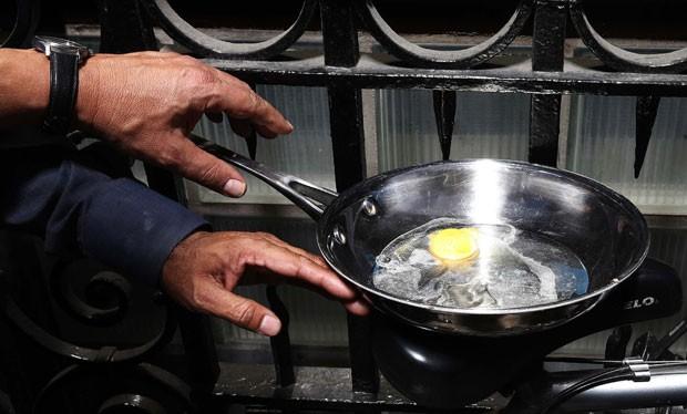 Homem chegou a fritar um ovo nesta quarta-feira (4) usando o reflexo do sol do polêmico arranha-céu de Londres  (Foto: Suzanne Plunkett/Reuters)