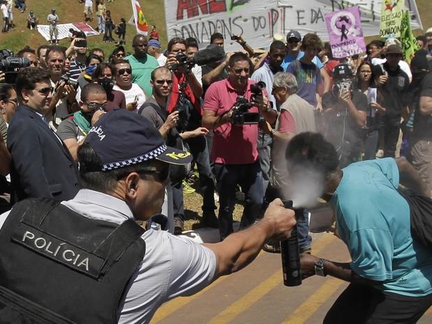 Policial militar usa spray de pimenta contra manifestante para dispersar protesto em Brasília. (Foto: Eraldo Peres/AP)