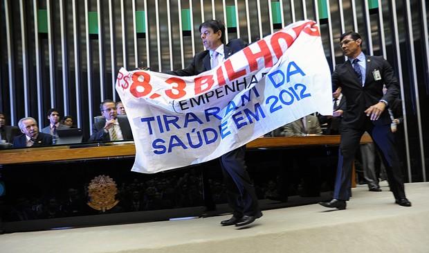 Toninho Pinheiro (PP-MG) sobe na Mesa da Câmara com faixa em protesto contra retenção de emendas da saúde (Foto: Laycer Tomaz/Ag. Câmara)