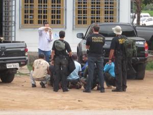 Os garimpeiros (agachados) foram levados à sede da Polícia Federal para prestar depoimento (Foto: Marcelo Marques/ G1)