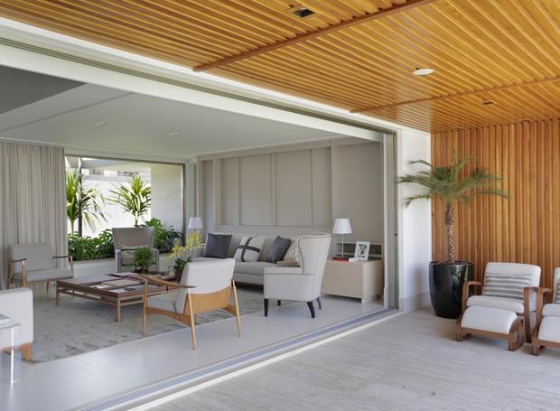 A varanda foi integrada à sala de estar e jantar. O teto e parede de madeira de freijó trazem mais aconchego ao espaço. Piso de mármore travertino romano bruto. Vaso da 6F Decorações (Foto: Denílson Machado - MCA Estúdio/Divulgação )