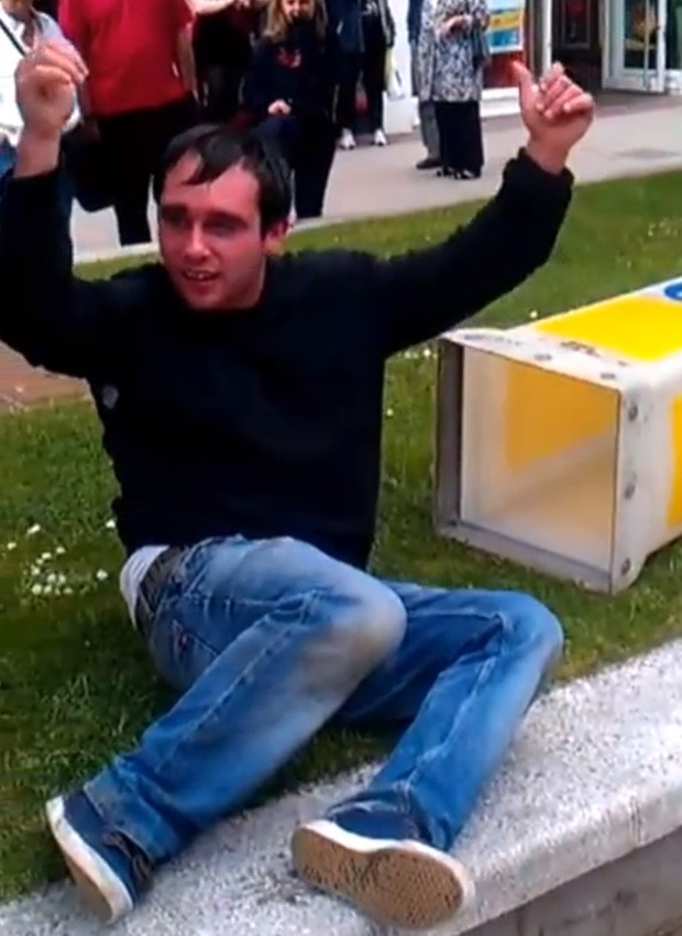 Após ser ajudado por amigos e policiais, rapaz foi libertar e acenou para o público presente (Foto: Reprodução/YouTube/John Waterman)