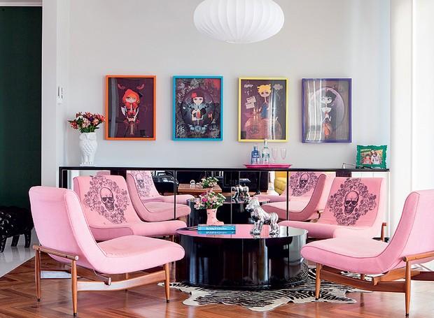 No espaço onde ficaria a mesa de jantar, a arquiteta Andrea Murao criou um lounge com mesa de centro baixa e aparador espelhado. Na parede, uma sequência de pôsteres (Foto: Lufe Gomes/ Editora Globo)