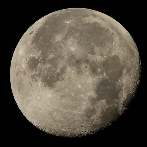 Foto mostra Estação Espacial Internacional (pequena mancha escura no centro) passando em frente à Lua (Foto: Nasa/Bill Ingalls)
