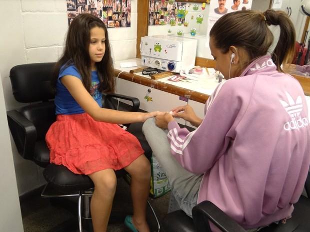 Sophia faz as unhas enquanto aguarda sua mãe (Foto: Salve Jorge/ TV Globo)