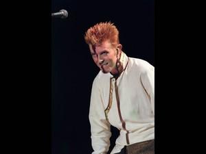 David Bowie faz show no Parc des Princes, em Paris, em junho de 1997. A sombra do microfone cortou seu rosto no momento da foto, lembrando maquiagem que ele usava em turnês do disco 'The rise and fall of Ziggy Stardust and the spiders from Mars', de 1972 (Foto: Jack Guez/AFP/Arquivo)