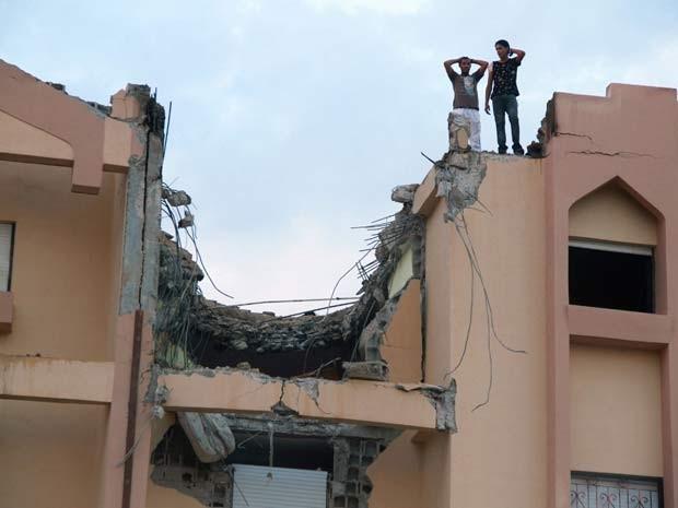 Moradores sobem a telhado destruído por queda de avião militar da Líbia nesta terça (2) (Foto: REUTERS/Stringer )