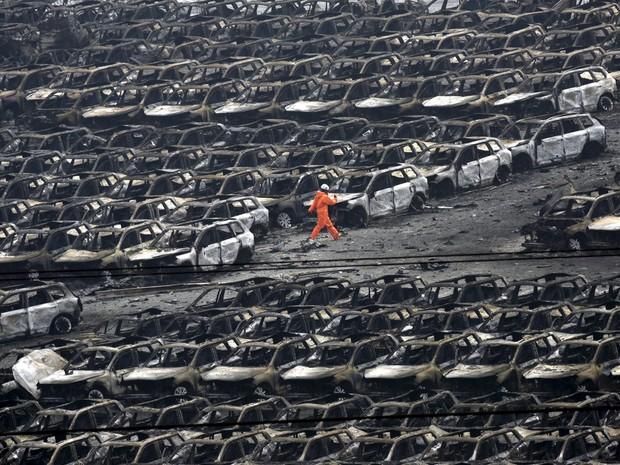 Bombeiro passa por carros destruídos no porto de Tianjin (Foto: REUTERS/Jason Lee)