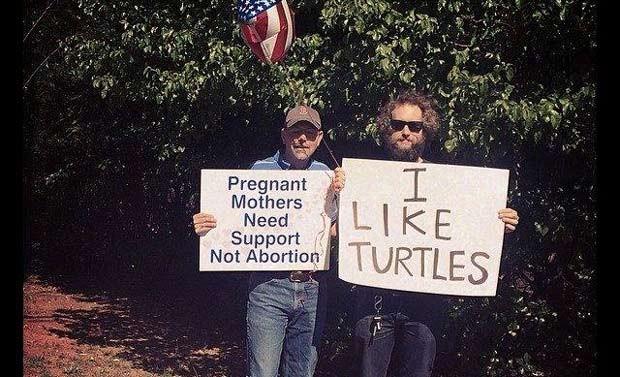 """Manifestante segura cartaz com a mensagem """"Mulheres grávidas precisam de apoio, não aborto""""; """"Eu gosto de tartarugas"""", diz cartaz de Grayson (Foto: Reprodução / Tumblr)"""