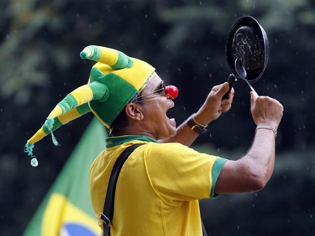 Com nariz de palhaço e batendo em uma panela, manifestante grita durante protesto na Avenida Paulista, em São Paulo (Foto: Paulo Whitaker/Reuters)