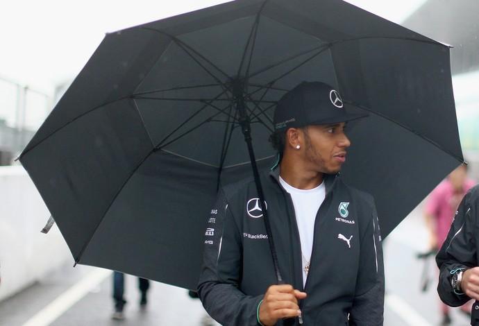 O líder do campeonato, Lewis Hamilton, segura guarda-chuva em visita a Suzuka nesta quinta-feira (Foto: Getty Images)