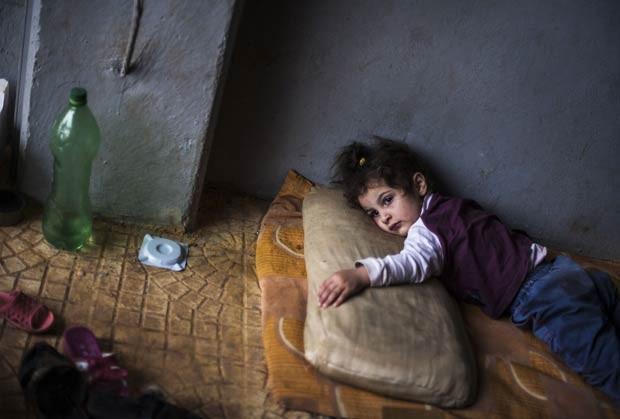 Menina refugiada síria em campo na fronteira com a Turquia, perto da vida de Azaz, neste domingo (30) (Foto: Manu Brabo/AP)