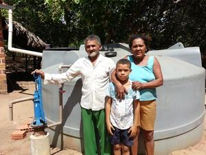 Raimundo e a família, que sofriam com a falta de distribuição de água, posam na frente de cisterna (Foto: Carlos Maciel)