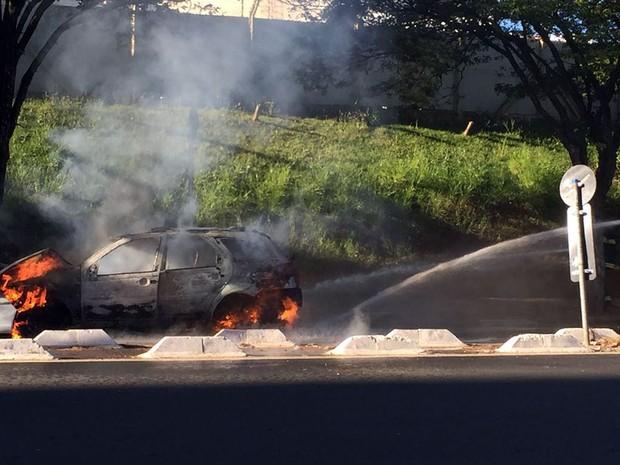 Bombeiro apaga incêndio de táxi em rua de Campinas (Foto: Vc no G1)