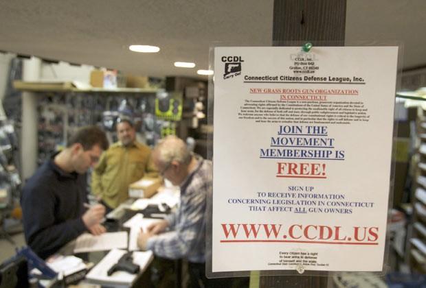 Homem preenche formulários para comprar arma em Guilford, no estado americano de Connecticut (Foto: AFP)