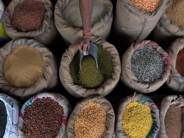 Um comerciante indiano pega grãos de um saco no jardim do Comitê de Produção e Mercado Agrícola (APMC, na sigla em inglês) em Bangalore, na Índia
