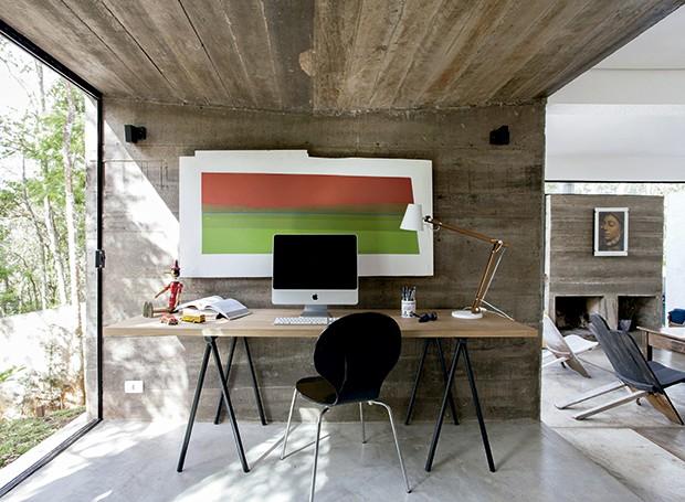 No escritório, a mesa é feita apenas com um tampo de madeira apoiado sobre dois cavaletes. Luminária da Tok & Stok e tela pintada pelo arquiteto (Foto: Marco Antonio/ Editora Globo)