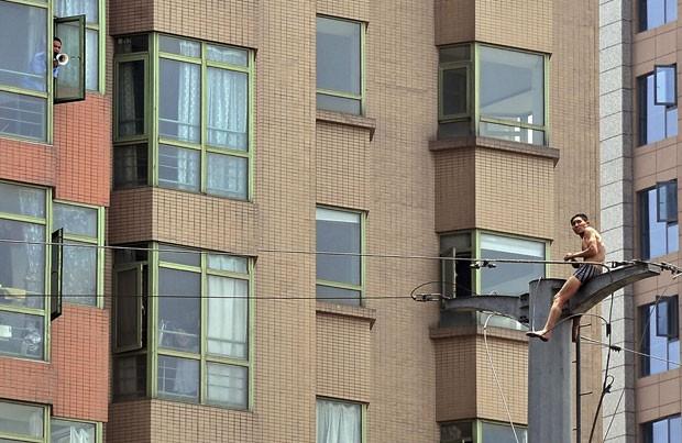 Homem escalou poste e ameaçou se jogar em Xi'an, na província chinesa de Shaanxi (Foto: Stringer/Reuters)