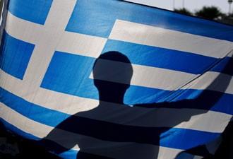 Manifestante ergue bandeira grega durante protesto em Atenas, em maio (Foto: Reuters)