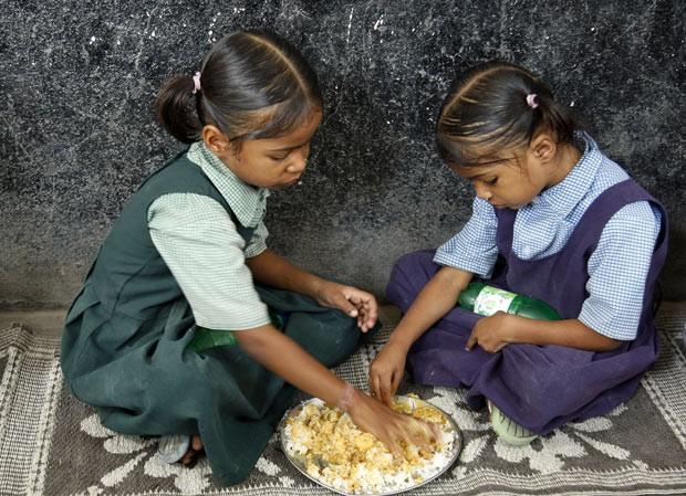 Meninas fazem refeição na escola na cidade de Hyderabad, na Índia. Programa indiano oferece refeições a 120 milhões de crianças nas escolas. (Foto: AP Photo/Mahesh Kumar A.)