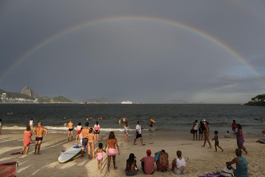 Banhistas observam arco-íris que apareceu no horizonte no último dia de 2013, na praia de Copacabana, no Rio de Janeiro