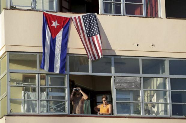 Vizinhos da Embaixada dos EUA em Havana assistem de longe a cerimônia de reabertura oficial do local. Com a presença do secretário de Estado dos EUA, John Kerry, a cerimônia teve o hasteamento da bandeira americana no prédio pela primeira vez em 54 anos, um marco na reaproximação dos dois países (Foto: Enrique de la Osa/Reuters)