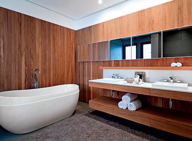 O tapete no piso e a peroba-rosa nas paredes aquecem o espaço em que a banheira Levitat, da Spas Versati, é o destaque. Projeto arquiteta Clarissa Strauss (Foto: Salvador Cordaro)