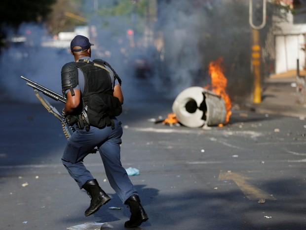 Policial corre para passar pela barricada durante confronto com estudantes em universidade na África do Sul (Foto: Siphiwe Sibeko/ Reuters)