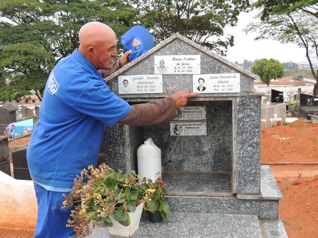 O coveiro cuida do túmulo onde está sepultada a esposa, falecida em maio deste ano (Foto: Pedro Carlos Leite/G1)