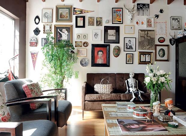 Para não gastar com pintura ou papel de parede, cubra as paredes com tudo o que tiver, como quadros, fotografias, louças e cabeças de bicho. Assim você esconde imperfeições na pintura e tem um visual incrível. Ideia da estilista Patricia Grejanin (Foto: Marcelo Magnani/Casa e Jardim)
