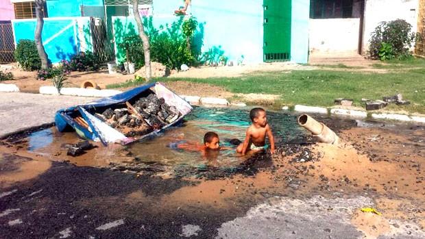 Tubulação da Caern rompe, abre cretera no meio da rua e crianças se arriscam tomando banho no buraco (Foto: Heloísa Lemos/G1)