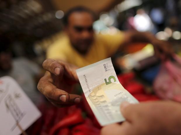 Vendedor pega uma nota de 5 euros em mercado de Atenas, nesta quarta-feira (8) (Foto: REUTERS/Christian Hartmann)
