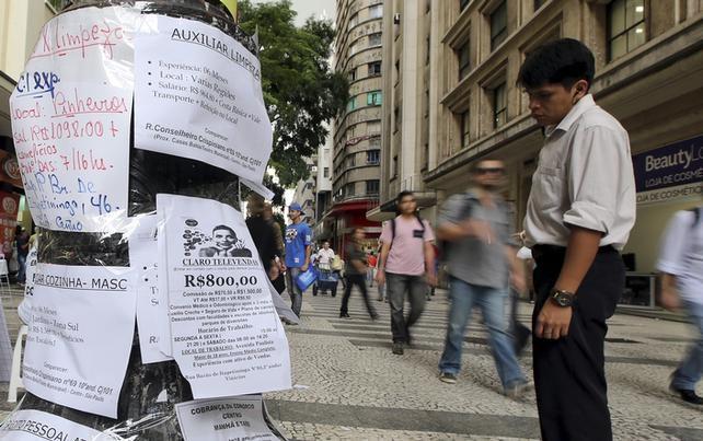 Homem olha para anúncios de empregos no centro da cidade de São Paulo