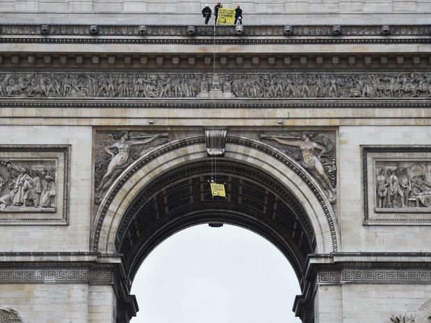 Ativistas do Greenpeace exibem uma faixa com os dizeres 'Senhor Hollande (presidente francês), renove a energia' no Arco do Triunfo em Paris, na França (Foto: Martin Bureau/AFP)