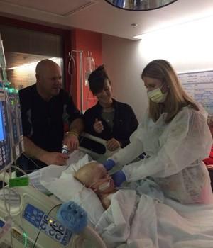 ESPERANÇA A família postou no Facebook a foto do momento em que o garoto recebe o medicamento (Foto: Reprodução / Facebook)