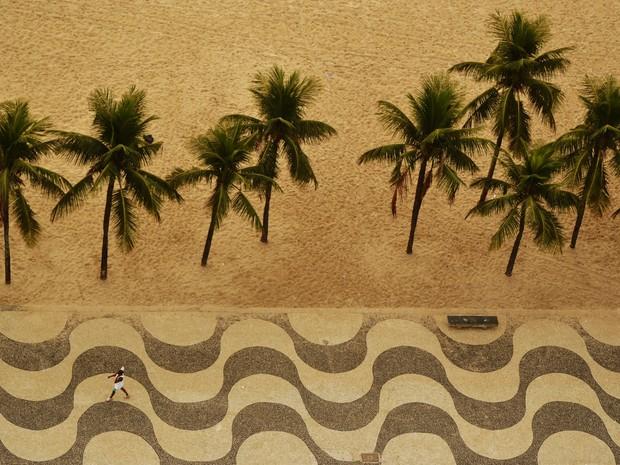 221b5af3c Uma pessoa caminha no calçadão durante amanhecer na praia de Copacabana