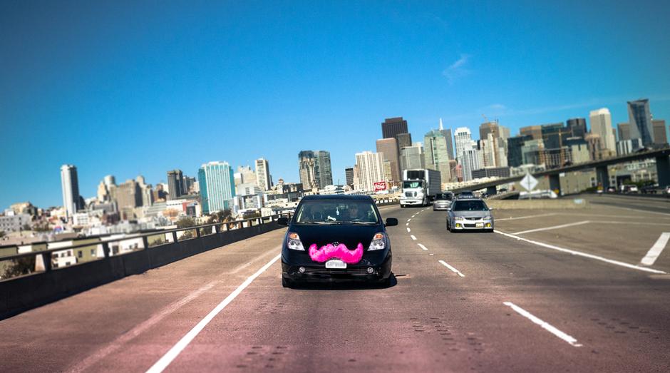 Famosa pelos bigodes rosas pendurados na frente dos carros que oferecem as caronas, a Lyft reúne pessoas que precisam de carona e motoristas dispostos a transportar desconhecidos (Foto: Divulgação)