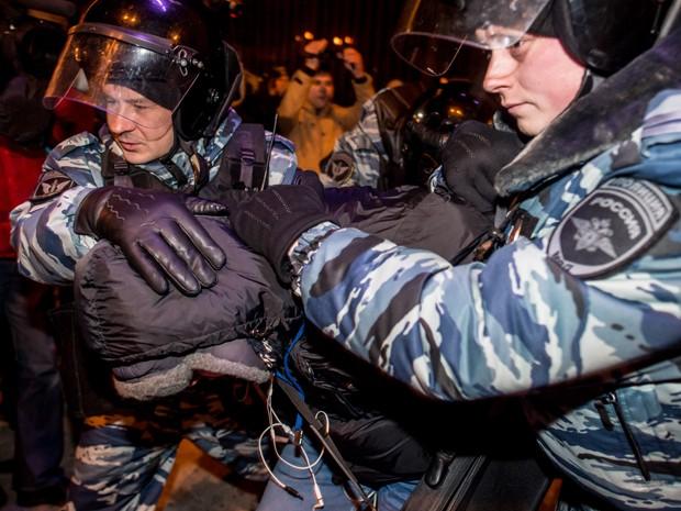Policiais prendem manifestante durante protesto em Moscou, na terça (30) (Foto: AFP Photo/Dmitry Serebryakov)