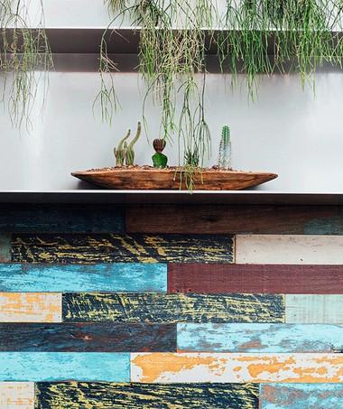 A madeira de demolição, pintada e desgastada, aparece nos painéis de parede e nas mesas (Foto: Ângelo dal Bó / Editora Globo)