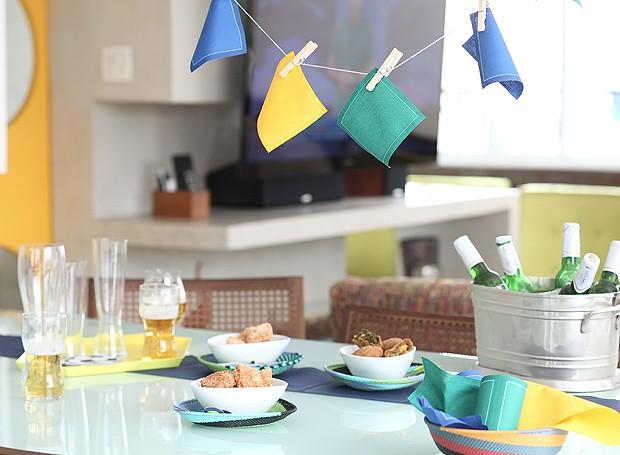 Guardanapos My Drap viram bandeirinhas patrióticas no varal montado sobre a mesa. No cardápio, almofadinha de camarão (em primeiro plano e à esq.) e bolinho de virado à paulista (à dir.), receitas de Katia Barbosa, do Aconchego Carioca. Bowls Benedixt, cestinhas Conceito Firma Casa, balde de gelo Cecilia Dale (Foto: Rogério Voltan/Editora Globo)