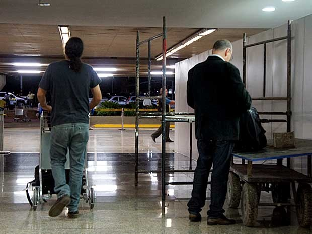 Passageiros desembarcam em meio a obras no Aeroporto JK; usuário usa carrinho como mesa para ver pasta (Foto: Ricardo Moreira/G1)