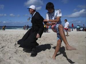 26/7 - Peregrinos vindos da Argentina, entre eles um padre, jogam futebol nas areias de Copacabana (Foto: Sergio Moraes/Reuters)