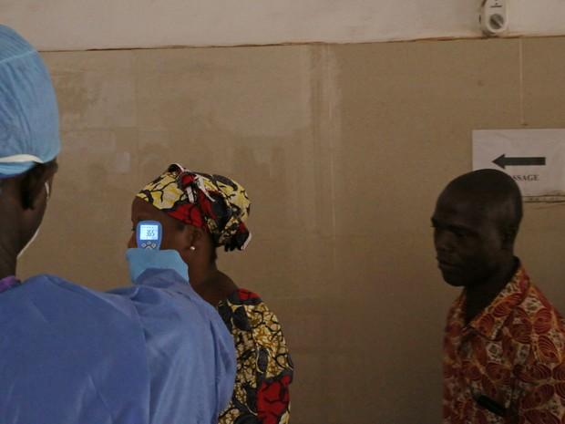 Profissional de saúde mede a temperatura de uma mulher para testar se ela pode estar infectada elo vírus ebola em hospital de Conakry, na Guiné, nesta sexta-feira (18)  (Foto: AP Photo/Youssouf Bah)