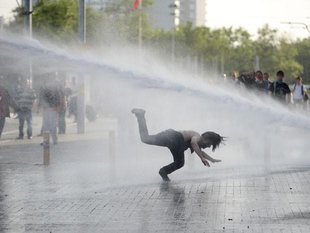 Manifestante tenta escapar de canhão de água disparado pela polícia para dispersar protesto contra a demolição do Parque Taksim Gezi, em Istambul, na Turquia, nesta sexta-feira (31). Segundo testemunhas, a polícia também usou gás lacrimogêneo para tentar acabar com o protesto. (Foto: AFP)