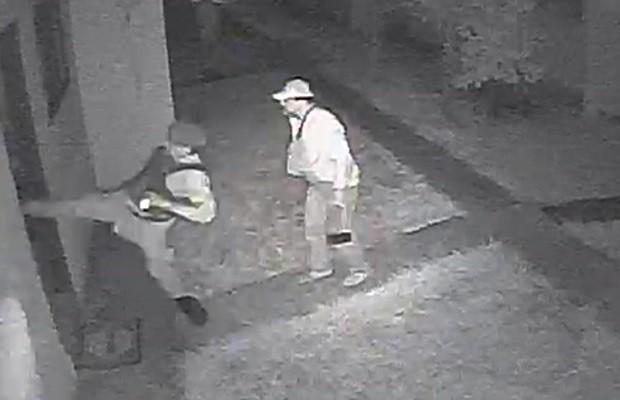 Homem fardado arromba porta da casa de vítimas, em Goiânia, Goiás (Foto: Reprodução/ TV Anhanguera)