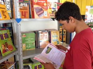 Estudante Rodrigo Costa espera ônibus praticando leitura em RO (Foto: Matheus Henrique/G1)