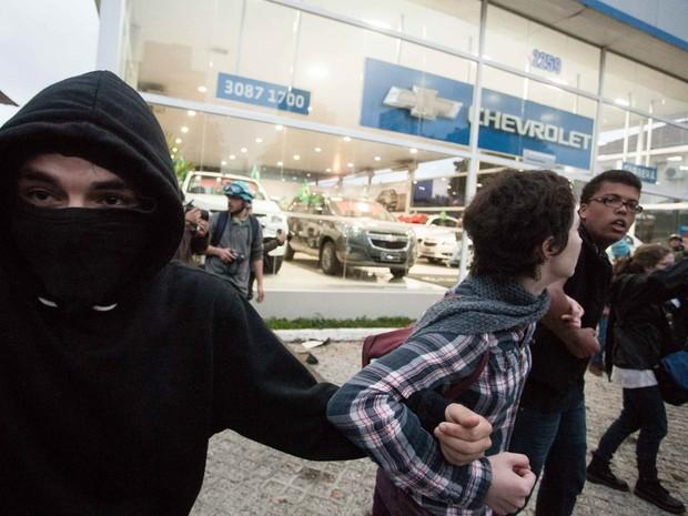 Manifestantes mascarados defendem agência de veículos contra depredação na avenida Rebouças, em São Paulo (Foto: Rodrigo Dionisio/Frame/Estadão Conteúdo)