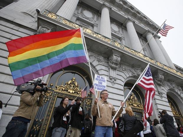 O californiano Billy Bradford segura bandeiras em frente à sede da Corte, em São Francisco, enquanto aguardava a decisão sobre o casamento gay, nesta quinta-feira (12) (Foto: Eric Risberg / AP)