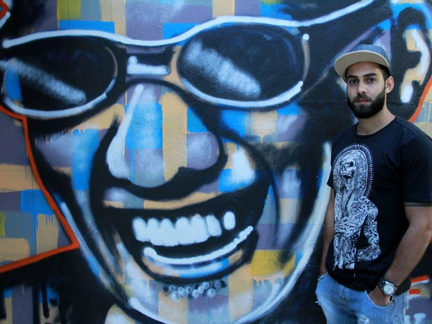 Thales França posa na frente de uma parede onde foi produzida uma de suas ilustrações (Foto: Waldson Costa/G1)